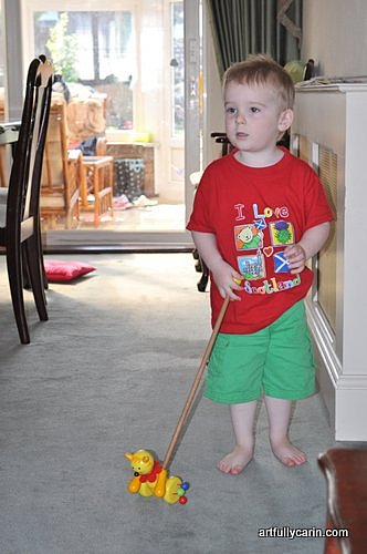 boy playing with wooden push along toy