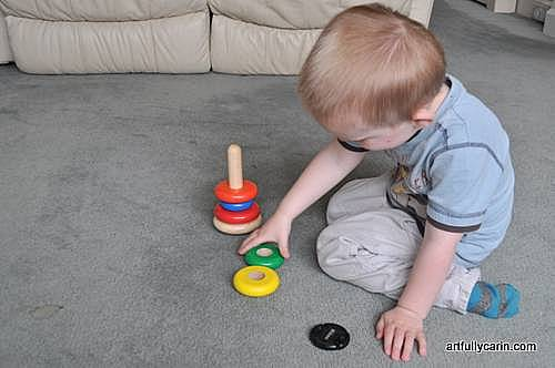 boy playing with stacking rings