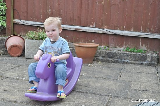 Boy on outdoor toy horse